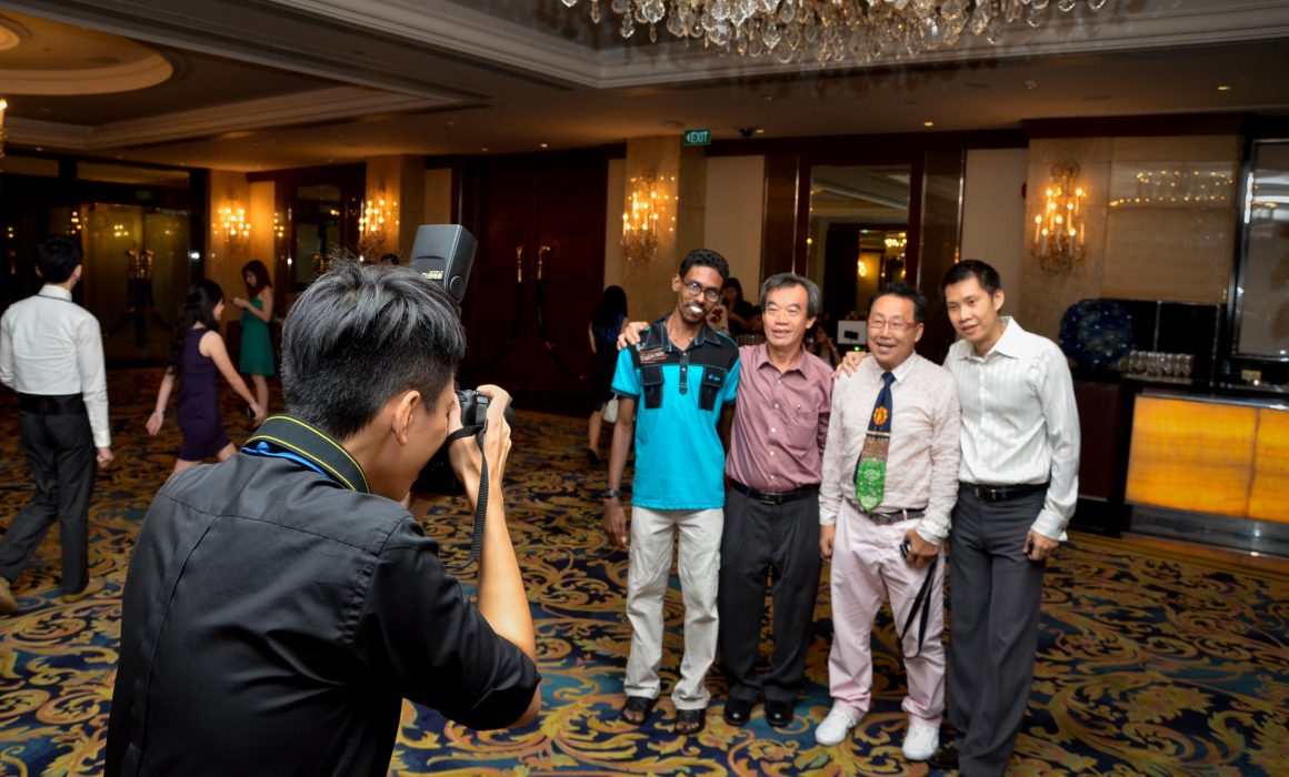 A roving photographer taking photos of a group of collegues