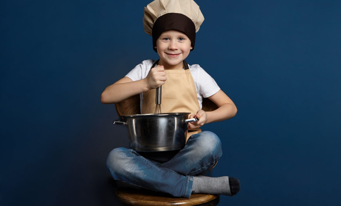 A generic photo of a young child wearing a chef's hat and holding on to a whisk and bowl