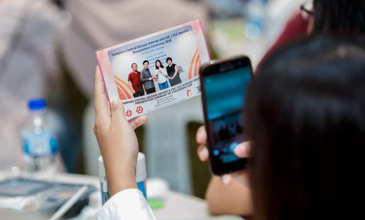 A person taking a photograph of their printed Edusave Awards photograph