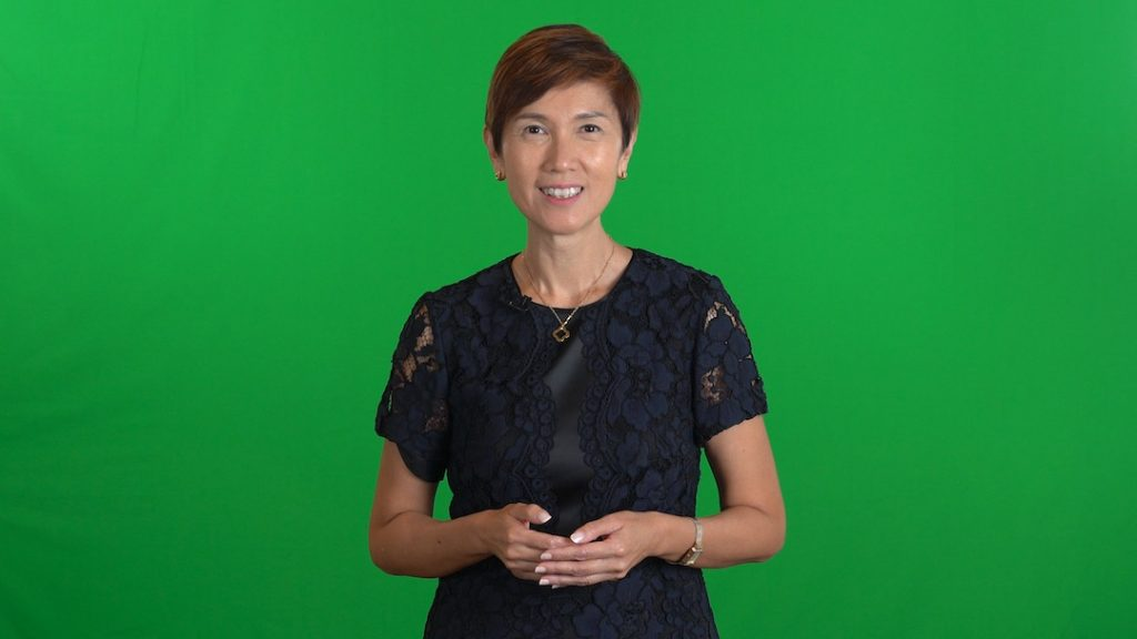 Minister Josephine Teo delivering her speech in front of a green screen backdrop.