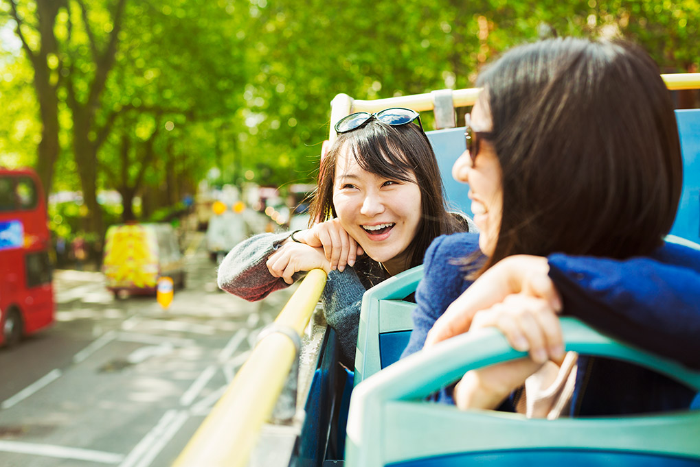 A generic photo of two Asian women on top a double-decker bus
