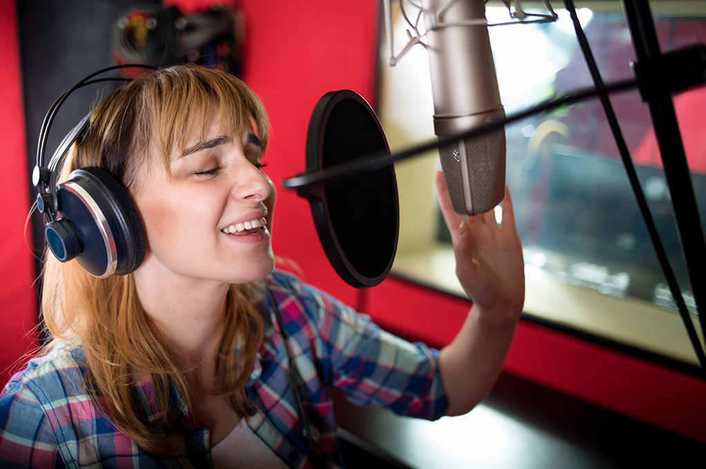 Lady speaking into a professional recording microphone